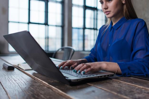 Imagem recortada de uma jovem funcionária trabalhando em um projeto de digitação de texto no laptop dentro de casa.