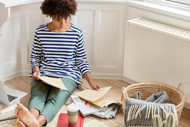 Imagem recortada de uma jovem mulher de pele escura em roupas casuais, olhando através de documentos
