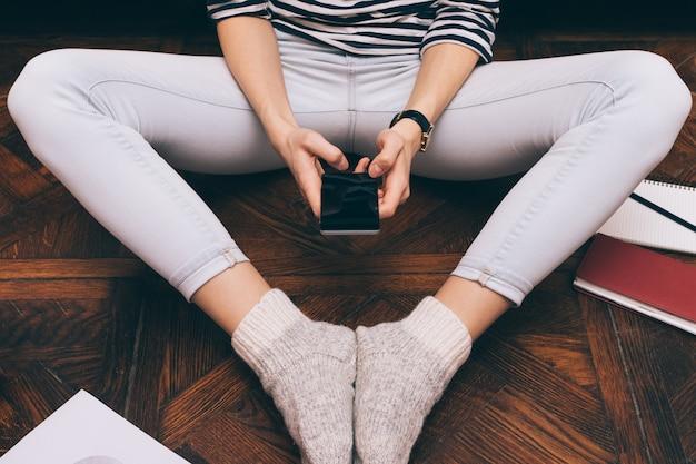 Imagem recortada de uma menina de jeans fica em casa no chão e usa um telefone inteligente