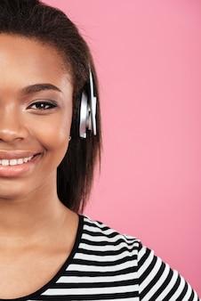 Imagem recortada de uma mulher adolescente sorridente feliz em fones de ouvido