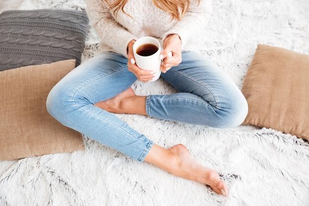 Imagem recortada de uma mulher de suéter e jeans segurando uma xícara de chá enquanto está sentada com as pernas cruzadas dentro de casa