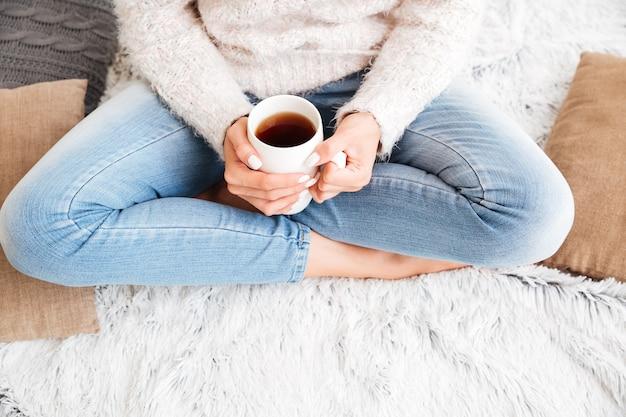 Imagem recortada de uma mulher de suéter e jeans segurando uma xícara de chá enquanto está sentada no tapete dentro de casa