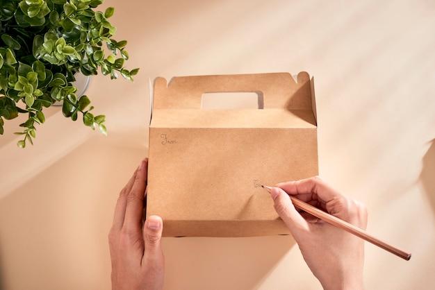 Imagem recortada de uma mulher escrevendo os melhores votos na caixa com um presente