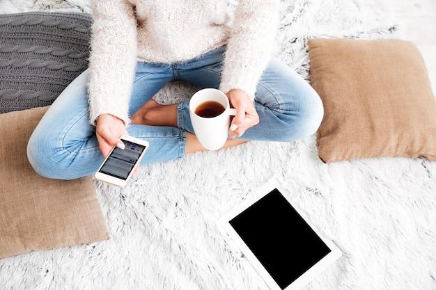 Imagem recortada de uma mulher segurando uma xícara de chá e um tablet com tela em branco enquanto está sentada no tapete em casa