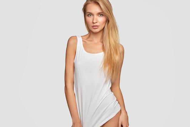 Imagem recortada de uma mulher séria de cabelos claros usando uma camiseta casual grande