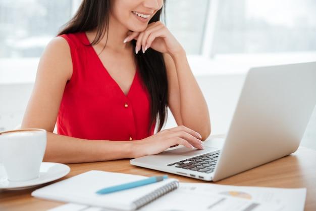 Imagem recortada de uma mulher sorridente de camisa vermelha sentada à mesa com um laptop no escritório