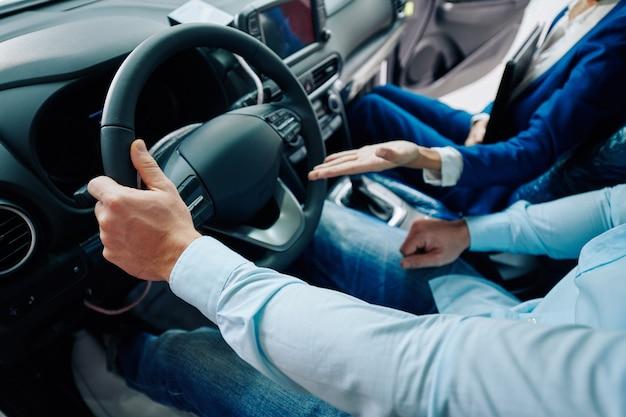 Imagem recortada do gerente da concessionária sentado no compartimento do carro com o cliente e mostrando as vantagens do novo modelo