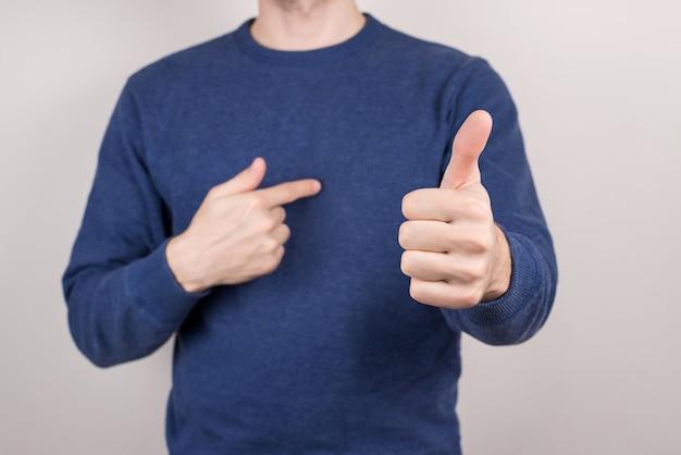 Imagem recortada do retrato da foto em close-up de um cara autodesenvolvido que se fez confiante, demonstrando o dedo no fundo cinza isolado