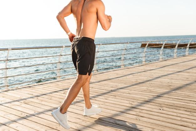 Imagem recortada, vista traseira de esportista correndo