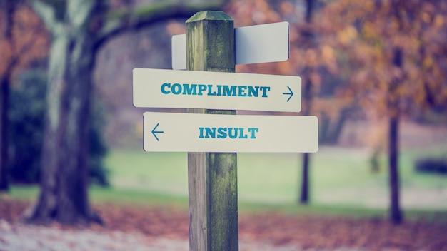 Imagem retro do estilo vintage de um quadro indicador rural com dois sinais dizendo - elogio - insulto - apontando em direções opostas.