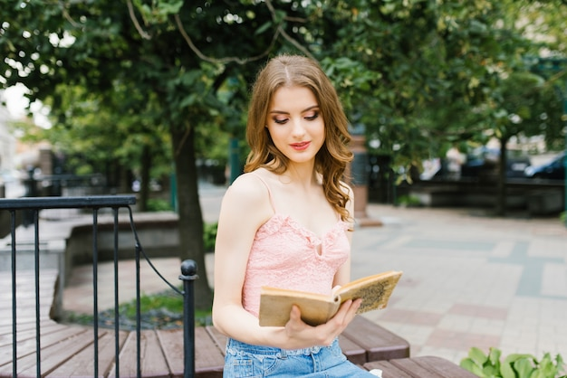 Imagem romântica de uma jovem andando em uma rua de verão no parque