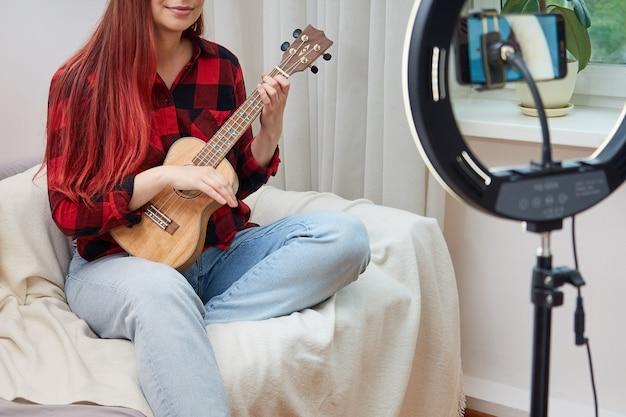 Imagem sem rosto de uma musicista blogueira fazendo transmissão ao vivo para assinantes