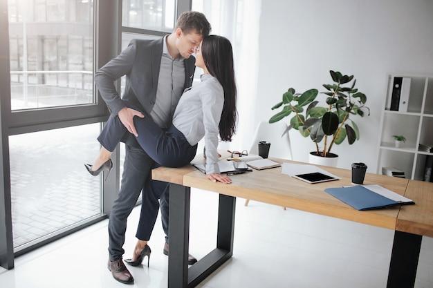 Imagem sexual e íntima do casal no trabalho. ela senta na mesa. ele segura a perna dela em pose sexual.