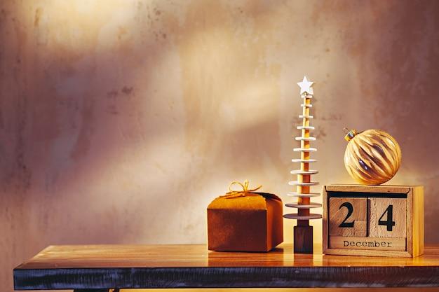 Imagem simples com árvore de natal, presente, enfeite e calendário de madeira