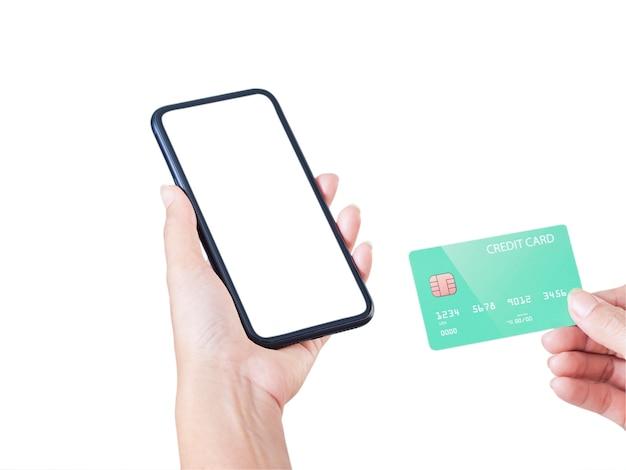 Imagem simulada da mão de uma mulher segurando um telefone celular, uma tela em branco e um cartão de crédito