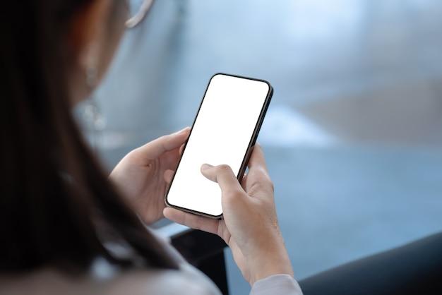 Imagem simulada vista traseira de uma mulher de negócios segurando uma tela em branco de telefones celulares