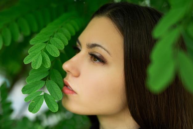 Imagem suave com maquiagem de uma linda mulher perto de folhas verdes