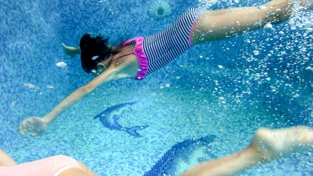 Imagem subaquática de uma adolescente em maiô listrado, mergulhando e nadando debaixo d'água na piscina
