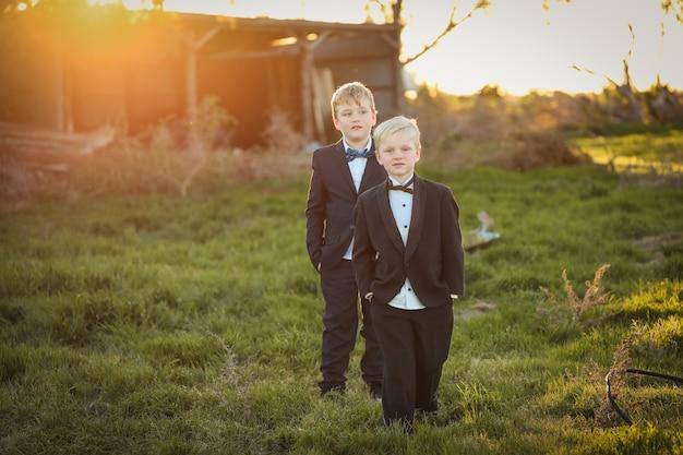 Imagem superficial de irmãos felizes de terno e gravata borboleta posando para a câmera