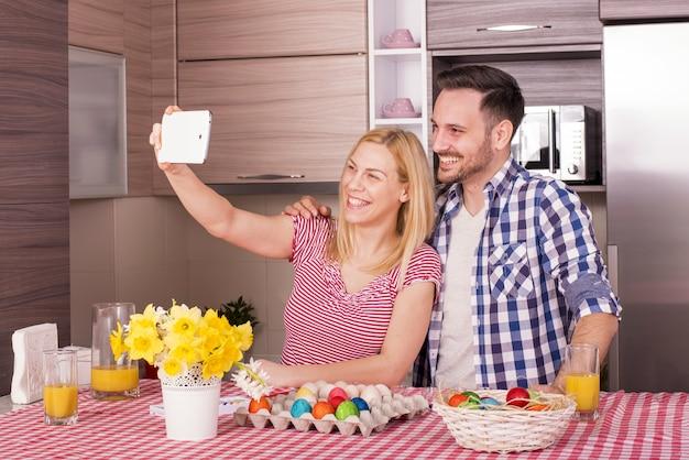 Imagem superficial de um casal feliz tirando uma selfie enquanto pinta ovos de páscoa com alegria