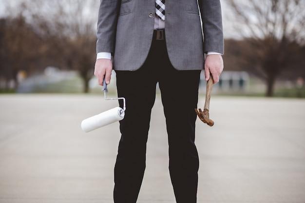 Imagem superficial de um homem segurando um martelo de madeira e um pincel de pintura na rua