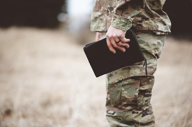 Imagem superficial de um jovem soldado segurando uma bíblia em um campo