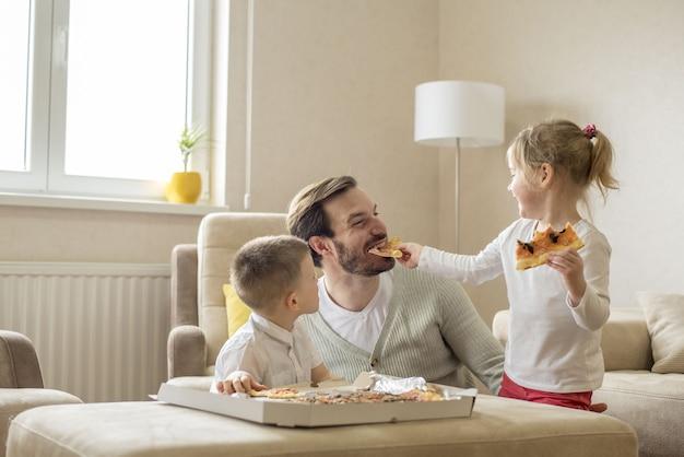 Imagem superficial de um pai caucasiano comendo pizza e se divertindo com os filhos