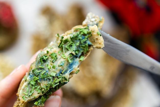 Imagem superficial de uma mão segurando pão vegan cru