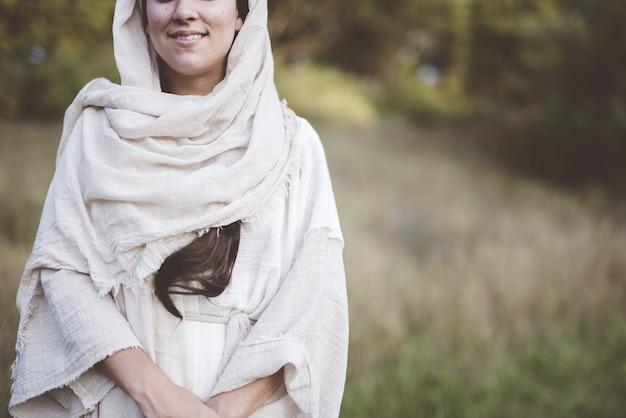 Imagem superficial de uma mulher vestindo um manto bíblico e sorrindo