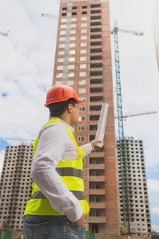 Imagem tonificada do arquiteto com capacete de segurança apontando para um prédio em construção