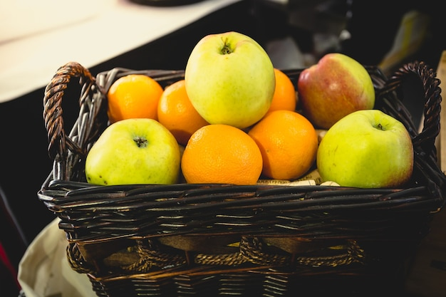 Imagem tonificada em close da cesta cheia de laranjas e maçãs verdes