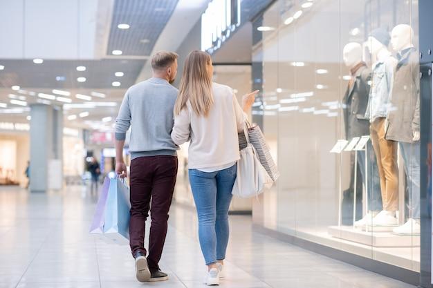 Imagem traseira de jovens compradores prestando atenção na nova coleção de roupas casuais masculinas na vitrine enquanto passam algum tempo no shopping