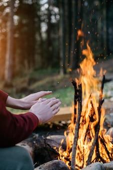 Imagem vertical ao ar livre do viajante que aquece suas mãos perto da fogueira na floresta.