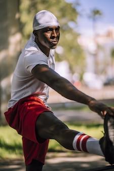 Imagem vertical com foco raso de um homem afro-americano com uma camisa branca se espreguiçando no parque