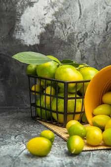 Imagem vertical da cesta preta com tangerinas verdes frescas e kumquats em jornais na mesa cinza.