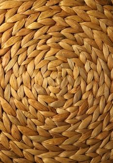 Imagem vertical da cor marrom dourada tecida da esteira de lugar do hyacinth de água para o fundo
