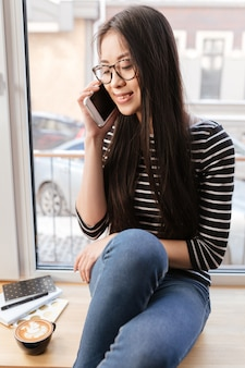 Imagem vertical da jovem mulher asiática falando telefone no peitoril da janela