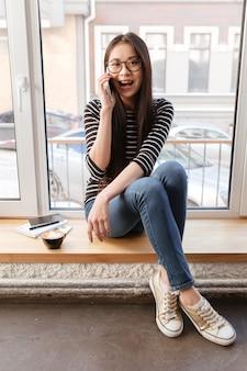 Imagem vertical da mulher asiática falando telefone no peitoril da janela