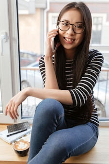 Imagem vertical da mulher asiática feliz falando de telefone no peitoril da janela
