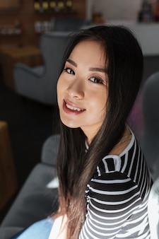 Imagem vertical da mulher asiática, sentado na cantina