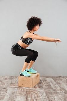 Imagem vertical da mulher sorridente fitness pulando na caixa