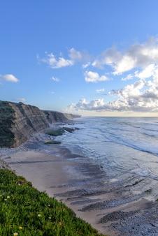 Imagem vertical da praia rodeada pelo mar e falésias ao sol e céu nublado