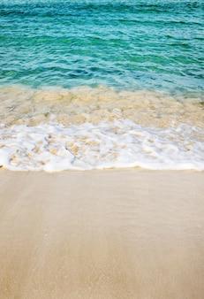 Imagem vertical da praia rodeada pelo mar sob o sol