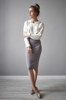 Imagem vertical de corpo inteiro de glamourosa jovem funcionária ou professora usando sapatos de salto alto em pé no estúdio em postura fechada com as pernas cruzadas, sendo tímido e tímido