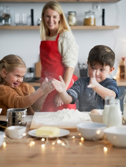Imagem vertical de crianças se agarrando com farinha enquanto assam biscoitos