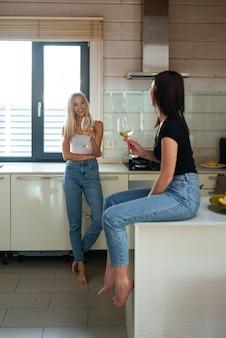 Imagem vertical de duas mulheres conversando na cozinha