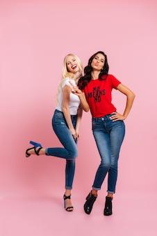 Imagem vertical de duas mulheres felizes posando no estúdio e olhando para a câmera sobre rosa