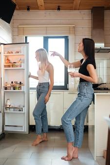 Imagem vertical de duas mulheres olhando para a geladeira