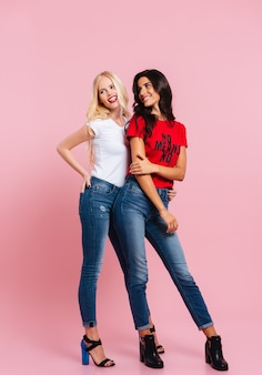 Imagem vertical de duas mulheres sorridentes posando no estúdio e olhando para a câmera sobre rosa