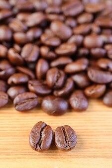 Imagem vertical de grãos de café torrados arábica vs robusta com a pilha de grãos de café borrados no fundo